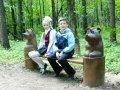 Деревянная скамейка в парке с резными скульптурами | Парковая скульптура