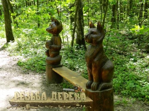 Деревянная скамейка с резными скульптурами