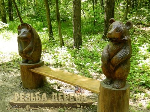 Парковая деревянная скамейка со скульптурами