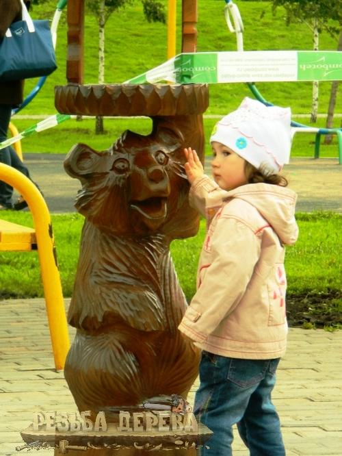 Девочка и деревянная скульптура