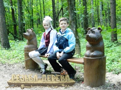 Деревянная скамейка в парке с резными скульптурами