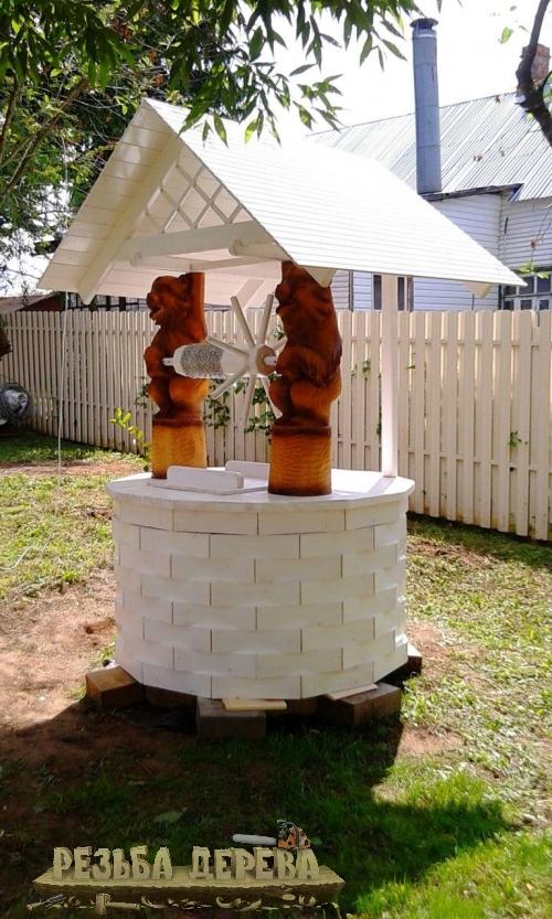 Белый колодезный домик с резными скульптурами